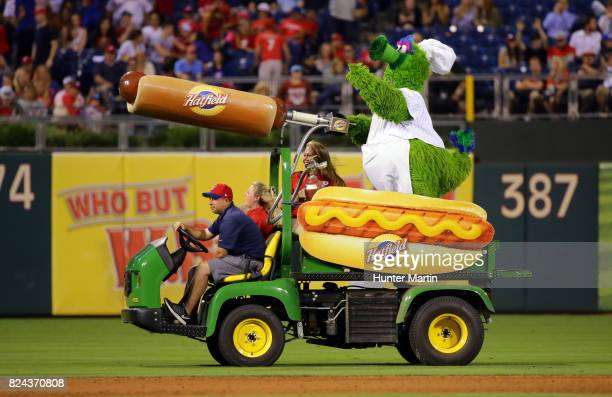 The Phillie Phanatic shoots hot dogs to fans sitting in the stands from a hot dog launcher during a game between the Houston Astros and the...