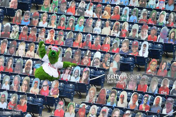 The Phillie Phanatic shows off the foul ball he caught amongst the cardboard cutout fans during an MLB baseball game between the Philadelphia...