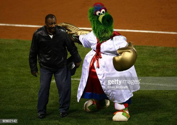 The Philly Phanatic mascot of the Philadelphia Phillies performs with an assist from Former heavy weight champion Joe Frazier against the New York...