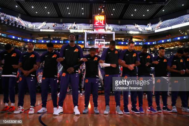 The Phoenix Suns stand arm in arm for the national anthem before the NBA game against the New Zealand Breakers at Talking Stick Resort Arena on...