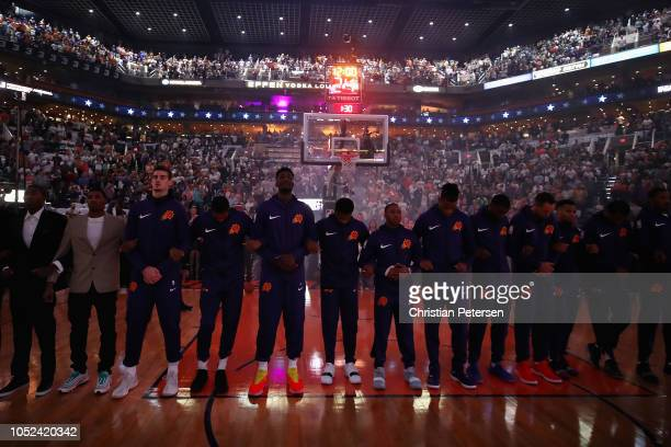 the Phoenix Suns stand attended for the national anthem before the NBA game against the Dallas Mavericks at Talking Stick Resort Arena on October 17...