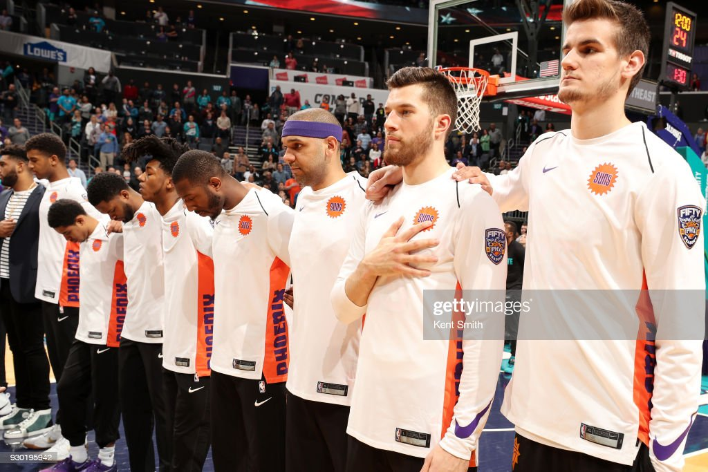 The Phoenix Suns stand for the National Anthem before the game against the Charlotte Hornets on March 10, 2018 at Spectrum Center in Charlotte, North Carolina.