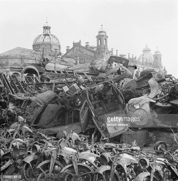 The photo by famous photographer Richard Peter sen shows a provisional scrap yard with wrecked vehicles in front of the ruins of the exhibition...