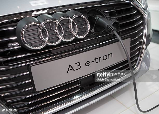The photo shows the front of an AUDI A3 e-tron with electric charging cable.