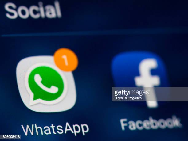 The photo shows the WhatsApp logo and the Facebook logo on the display of a smartphone