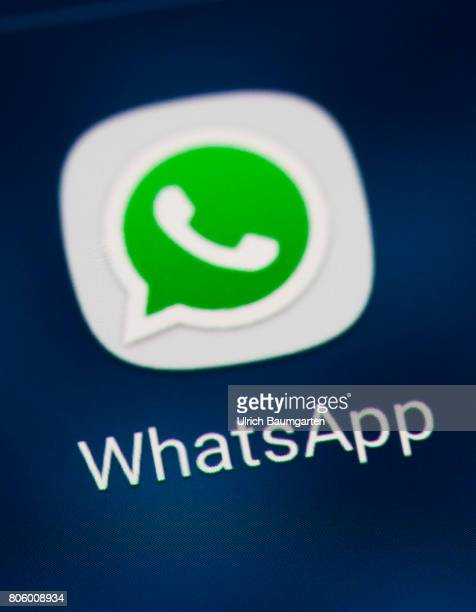 The photo shows the WhatsApp logo on the display of a smartphone