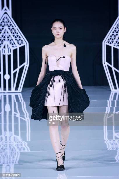 The photo taken on October 28 2020 shows a model displaying a creation from the OU collection designed by Xu Hua during China Fashion Week in Beijing...