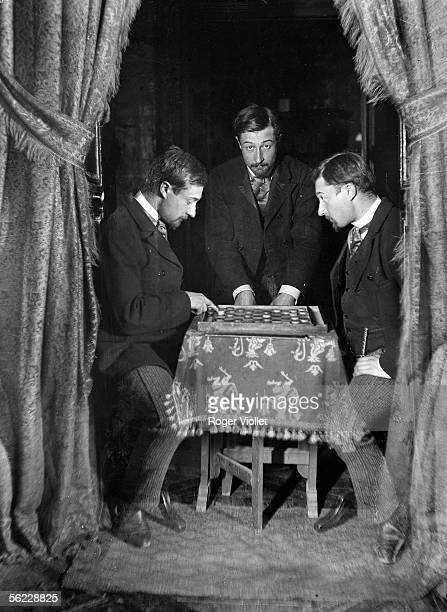 The photographer looking himself playing draughts with his double 'Trilocation' effect of Henri Roger
