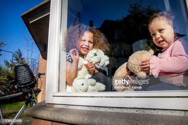 The photographer's children are seen in the window of a house as they participate in a 'teddy bear hunt' on March 29, 2020 in The Hague, Netherlands....
