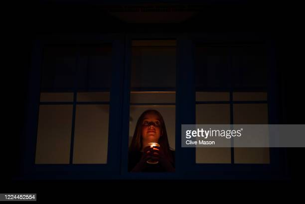 The photographers daughter Hollie, holds a candle at her bedroom window to mark International Nurses Day and the 200th Anniversary Of The Birth Of...