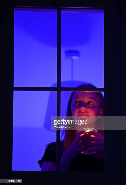 The photographers daughter Hollie holds a candle at her bedroom window to mark International Nurses Day and the 200th Anniversary Of The Birth Of...
