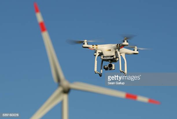 The photographer's DJI Phantom 3 Pro multirotor drone flies near a wind farm on June 8 2016 near Brueck Germany Countries across Europe are debating...