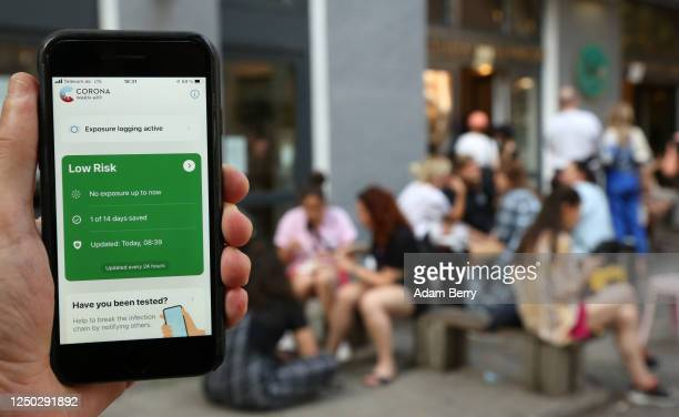 The photographer's hand holds an Apple iPhone showing the German federal health ministry's CoronaWarnApp software on the day after the app's release...