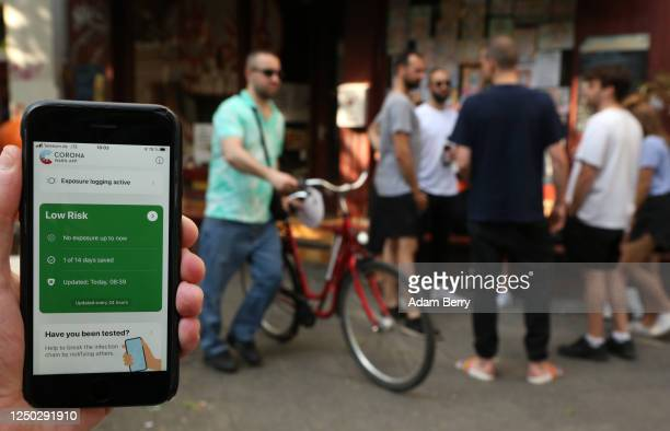 The photographer's hand holds an Apple iPhone showing the German federal health ministry's Corona-Warn-App software, on the day after the app's...