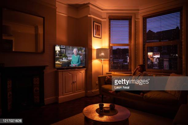 The photographer's partner watches as Queen Elizabeth II addresses the nation in a special broadcast to the United Kingdom and the Commonwealth in...