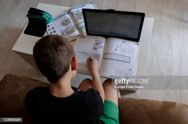 The photographer's son and primary school student does his homework in English with several books and a computer less than a month away from...