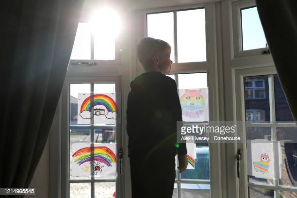 The photographer's son looks out of a window of his home after drawing a rainbow picture on March 26 2020 in Stockport England British Prime Minister...