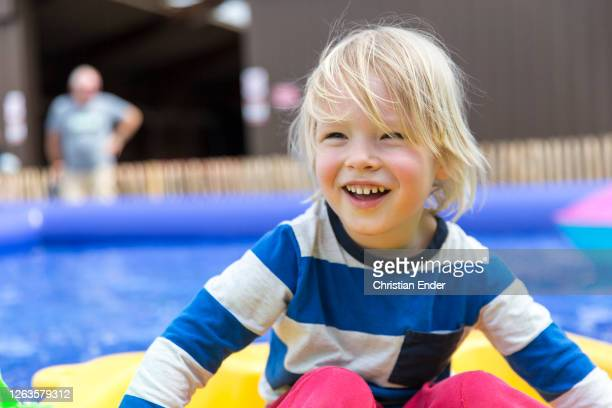 The photographers son plays on a paddling pool with a small boat at a fair during the coronavirus pandemic on July 19, 2020 in Einbeck, Germany.