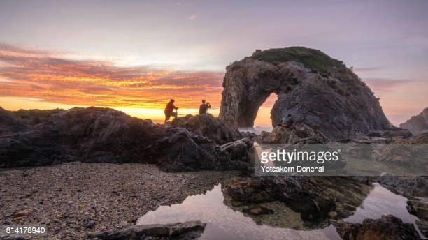 The photographers taking a photo of sunrise over Horse Head Rock, Bermagui, Australia