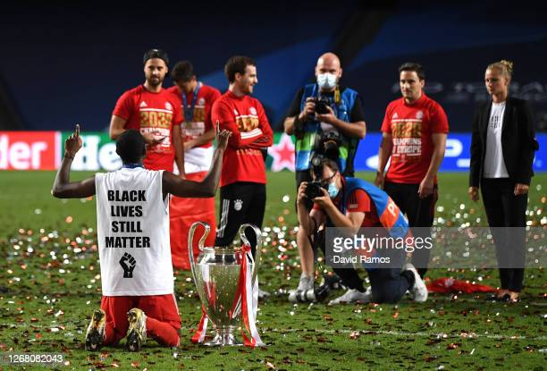 The phrase 'Black Lives Still Matter' is seen on the back of David Alaba of FC Bayern Munich's shirt as he celebrates with the UEFA Champions League...