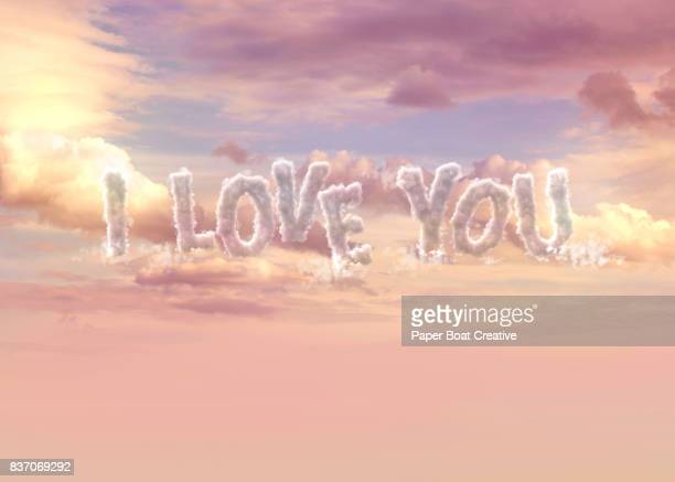 the phrase i love you formed using clouds with a pinkish sunset in the background - typographies stock photos and pictures