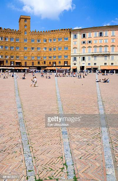 The Piazza del Campo and surrounding buildings with tourists walking in the square