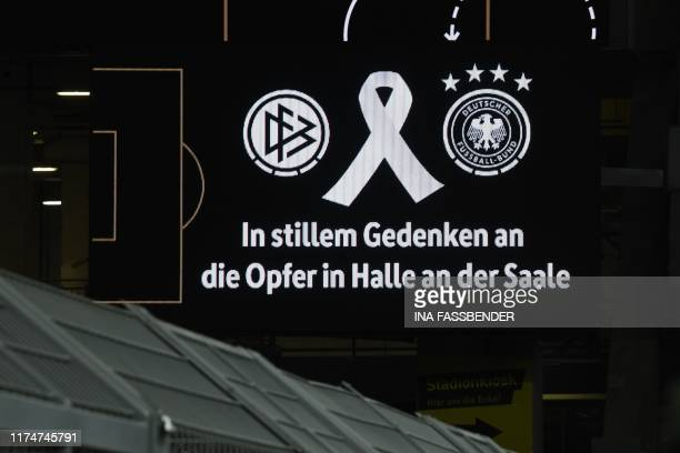 The picture shows a video screen during a minute of silence for the victims of a shooting at a synagogue in Halle prior to a friendly soccer match...