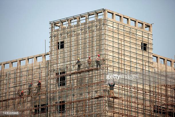 The picture taken on April 18, 2012 shows migrant workers on scaffolding at a construction site in Huaibei, in eastern China's Anhui province. New...