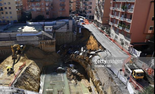 TOPSHOT The picture taken on February 15 2018 in the street of Balduina's district in Rome shows a general view of a huge sinkhole that opened up the...