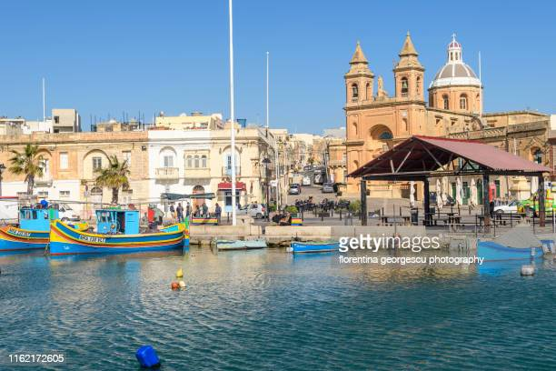 the picturesque harbor with colorful luzzu fishing boats and the church of our lady of pompeii at marsaxlokk, malta - marsaxlokk stock pictures, royalty-free photos & images