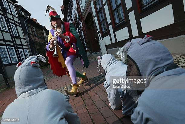 The Pied Piper of Hamelin actually city tourism employee Michael Boyer leads local children dressed as rats through a quiet street on November 19...