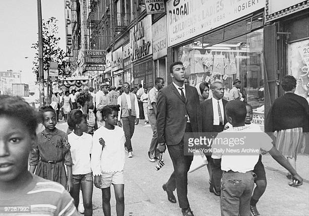 The Pied Piper of Harlem Cassius Clay whistling a sweet tune as he nonchalantly strolls down a street in Harlem