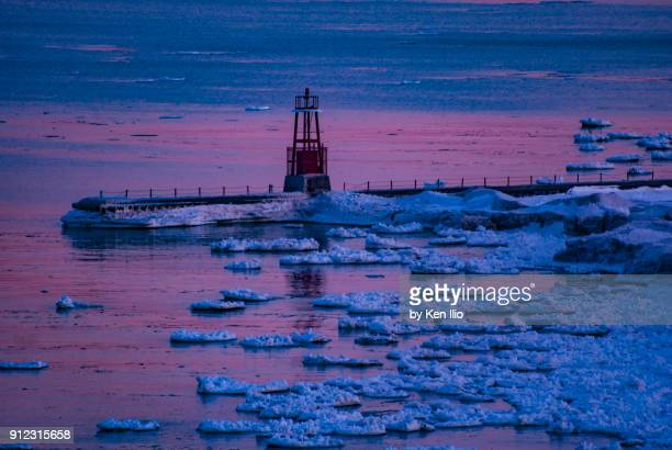 The pier with beacon on icy water