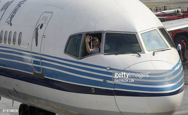 The pilot of the Xiaman Airline plane carrying the first group of Chinese tourists to arrive in Taipei from Xiamen waves from the cockpit as landing...