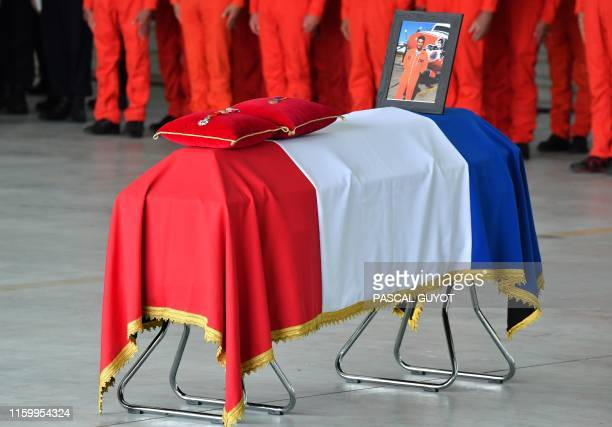 The pilot's portrait and the badge of the French Legion of Honour are displayed on the coffin during a ceremony in Nimes on August 6 2019 in tribute...