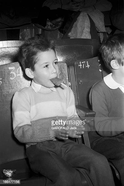 The Pinder Circus Le 07 janvier 1956 dans les gradins du cirque PINDER pendant un représentation un petit garçon à placé sa glace dans sa bouche pour...