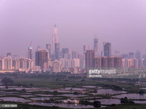 The Ping An International Finance Center center left and other buildings in Shenzhen stand shrouded in smog beyond farmland in the Ma Tso Lung...