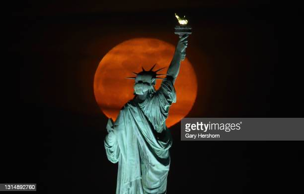 The pink moon rises above the Statue of Liberty in New York City a day after being full on April 27, 2021 as seen from Jersey City, New Jersey.