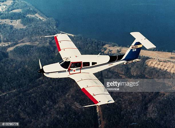 The Piper PA28 Arrow modified for the spin tests flies above a shoreline