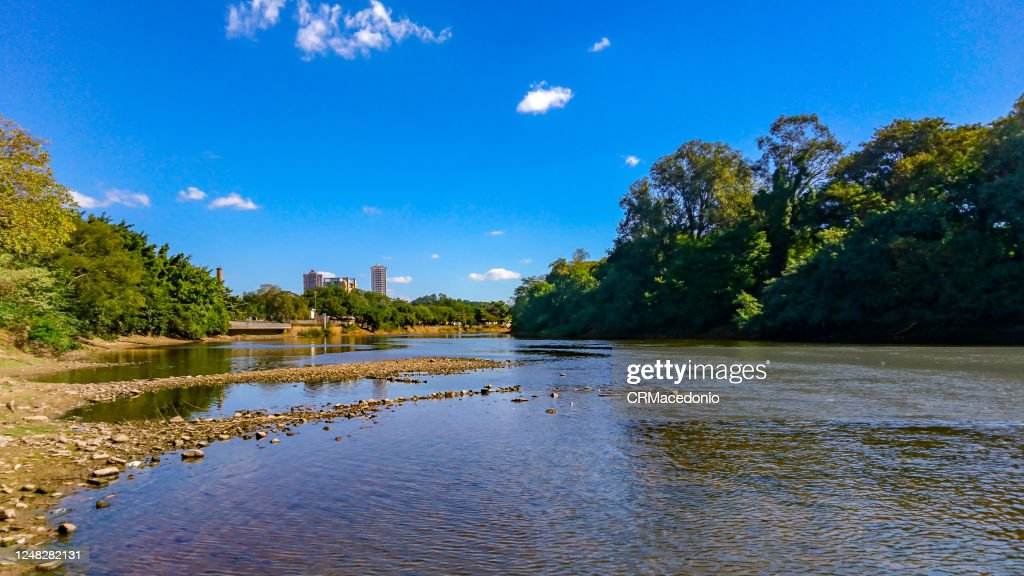 The Piracicaba River in a dry season, under blue sky between clouds. : ストックフォト