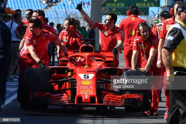 The pit crew of Ferrari's German driver Sebastian Vettel push his car back to the garage after scrutineering before the first Formula One practice...