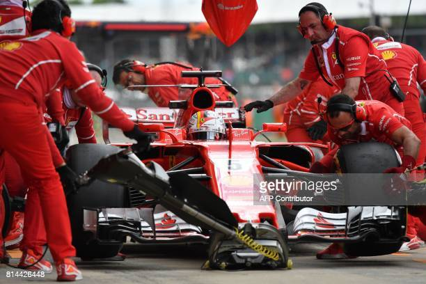 The pit crew rehearse a tyre change on Ferrari's German driver Sebastian Vettel during the second practice session at the Silverstone motor racing...