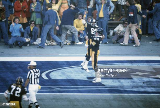 The Pittsburgh Steelers' Lynn Swann is held up by his teammate in celebration and gestures to the rest of his team from the end zone during Super...