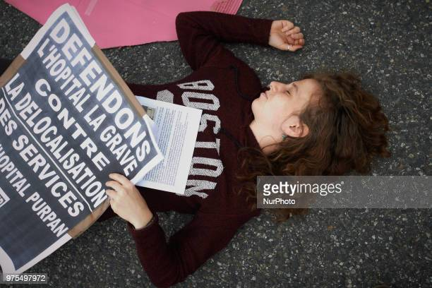 The placard reads 'Let's us defend the La Grave hospital against relocation' Several ONGs as Act'up organized a diein near the La Grave hospital in...