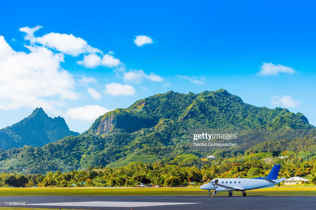 The plane at the airport on a background of mountain scenery, Aitutaki Island, Cook Islands. Copy space for text : Stock Photo