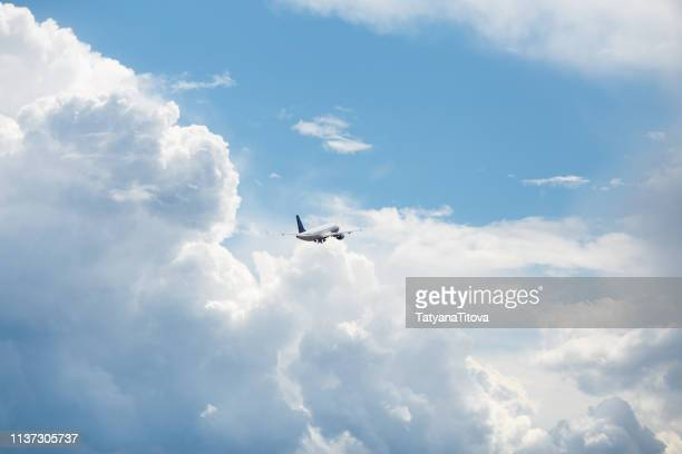 the plane flies in the blue sky into the beautiful clouds - airbus a320 stock pictures, royalty-free photos & images