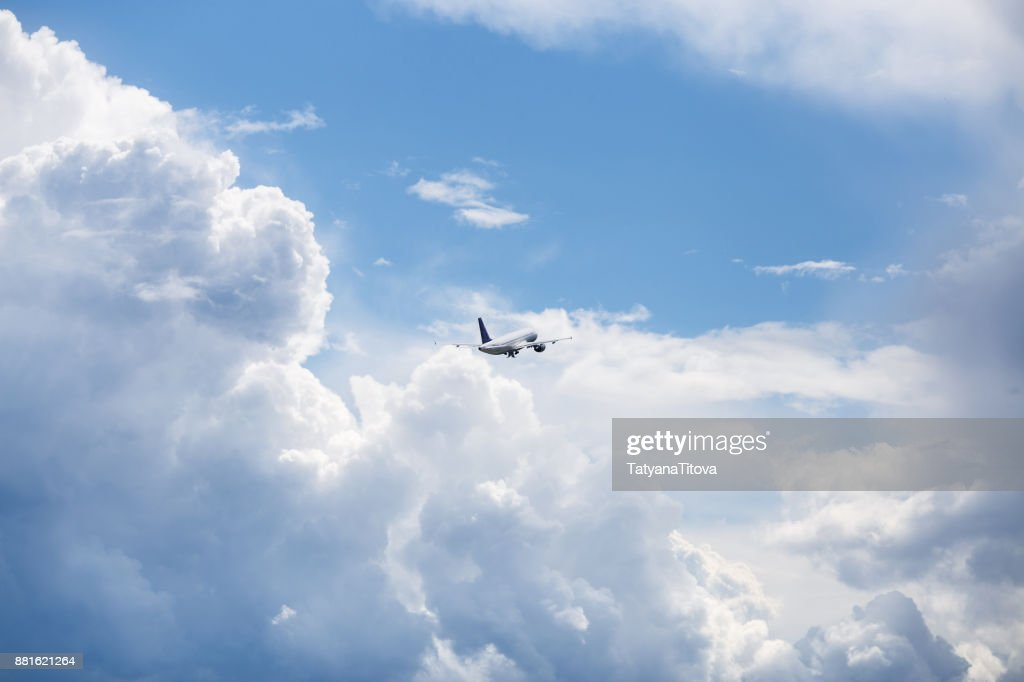 the plane flies in the sky in beautiful clouds : Stock Photo