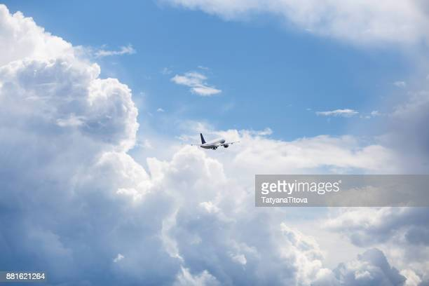 the plane flies in the sky in beautiful clouds