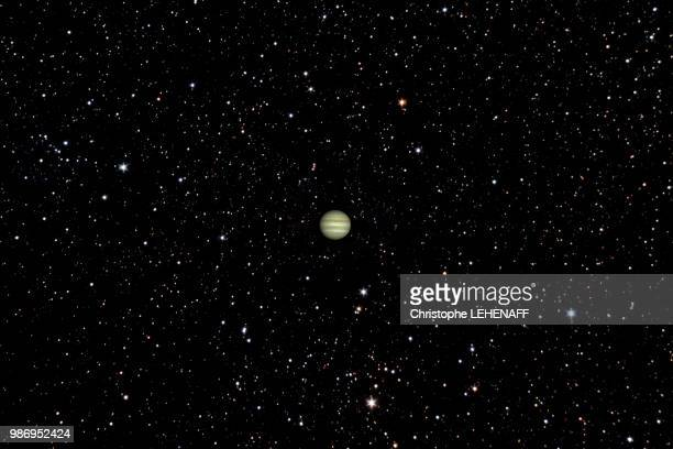 The planet Jupiter shines in front of hundreds of stars.