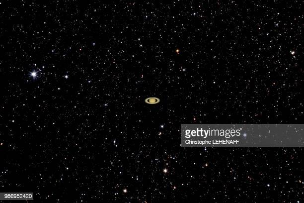 the planet saturne shines in front of hundreds of stars. - saturn planet stock pictures, royalty-free photos & images